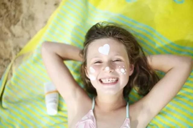 Petite fille avec de la crème solaire sur le visage