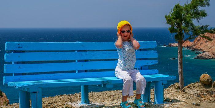 Petite fille assise sur un banc au bord de la mer