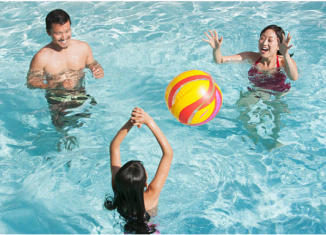 famille qui joue au ballon dans une piscine