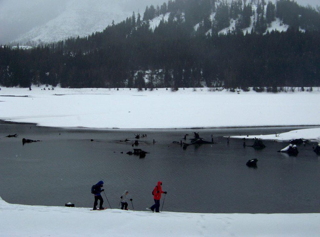 Personnes pratiquant les raquettes autour d'un lac au pied d'une montagne enneigée