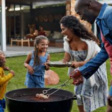 famille de deux adultes et deux enfants autour du barbecue