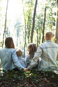 famille de deux adultes et deux enfants portant des veste en jean assorties assis dans la forêt