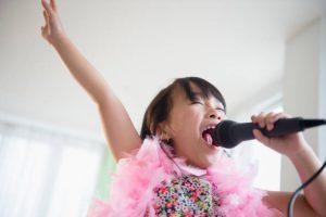 Petite fille déguisée en train de chanter dans un micro