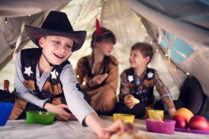 Groupe d'enfants en train de jouer sous un tipi et déguisés en cowboys et indiens