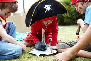 Enfants déguisés en pirates en train de regarder une carte au trésor dans le jardin