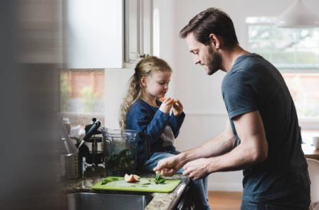 un papa et sa fille dans la cuisine qui préparent le repas