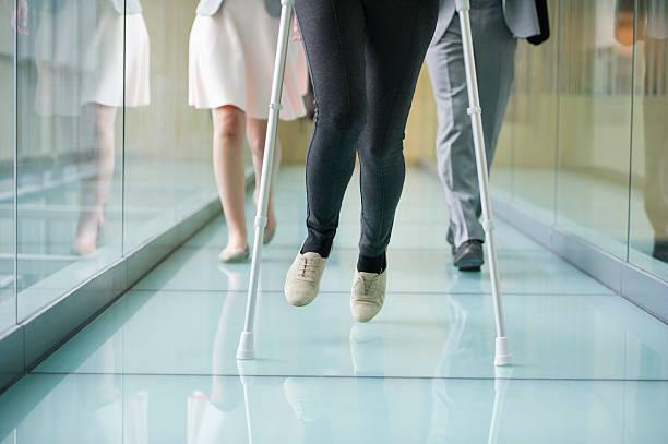 Femme qui marche en béquilles dans un couloir d'hopital