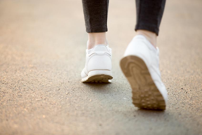 Gros plan surr les chaussures blanches d'une femme qui court