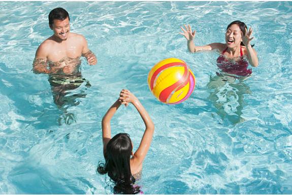 deux parents et leur enfant qui jouent au ballon dans une piscine