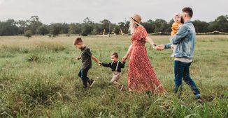 Plusieurs membres d'une famille, parents en enfants, qui courent dans un champ en se tenant par la main