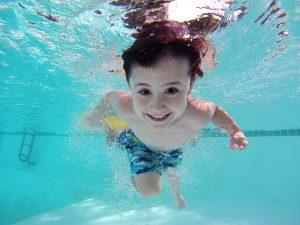 enfant sous l'eau qui sourit dans une piscine