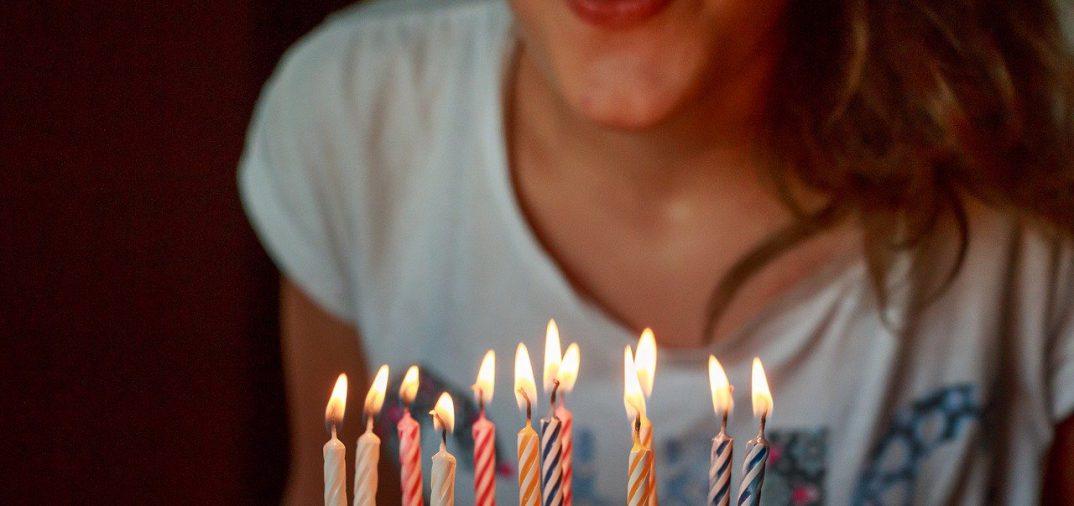 personne qui souffle les bougies sur son gateau d'anniversaire