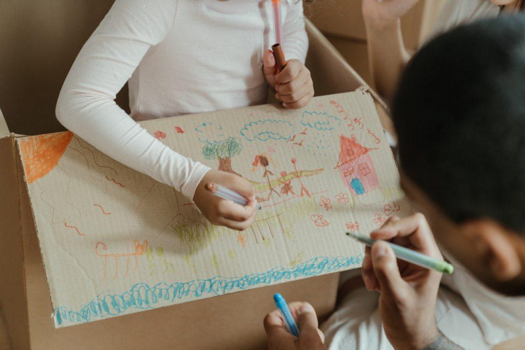 enfant qui dessine sur un carton de déménagement