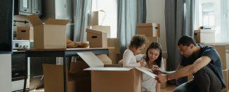 enfant assise dans un carton et qui dessine dessus avec ses parents