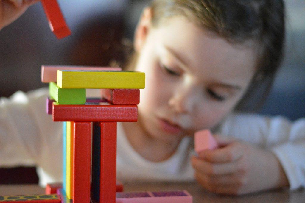 petite fille qui joue avec des cubes de construction