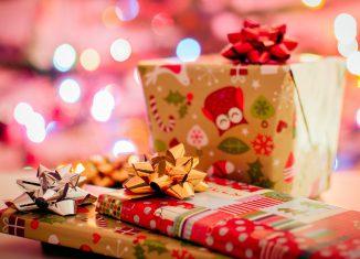 Plusieurs cadeaux de Noël posés sur une table et emballés dans du papier cadeau avec noeud en ruban sur le dessus